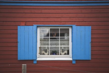 Blaues Fenster an rotem Haus.